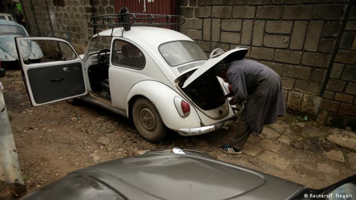 An old VW Beetle being refutbished by an African mechanic