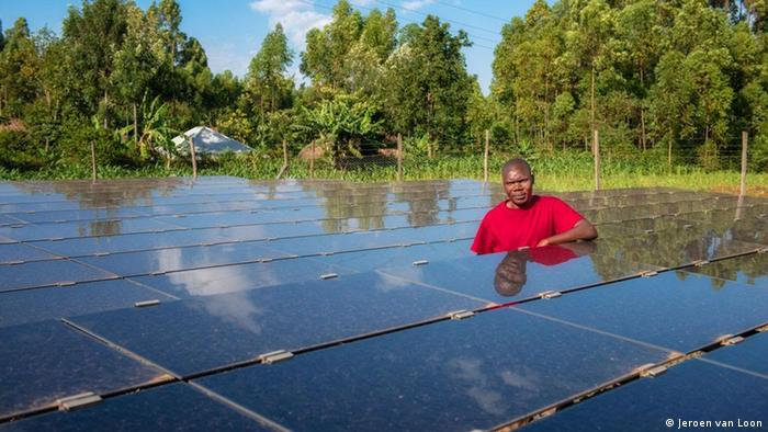 A man stands next to a solar mini grid in Kenya