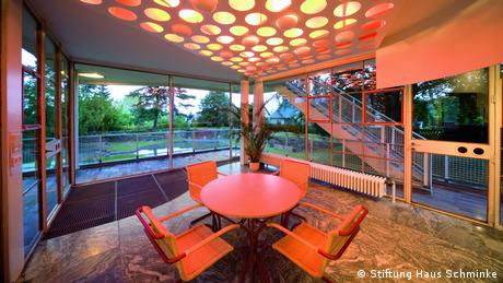 The large sliding glass door leads directly from the living room to the winter garden. Here, the holes and lights in the ceiling set a particularly interesting mood. The extra holes in the doors were made for children, and their colorful pattern can be found in the whole house. (Stiftung Haus Schminke)
