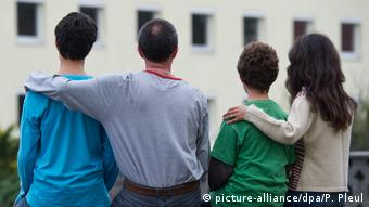 A family stands with its back to the camera and arms around one anothe