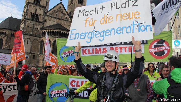 Klimaaktivist wirbt für den starken Ausbau der erneuerbaren Energien auf einer Demonstration in Bonn