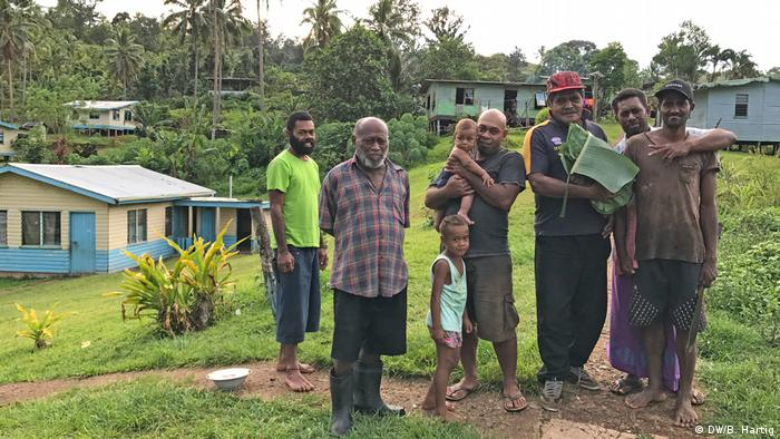 A group of villagers in Fiji in standing in front of some houses