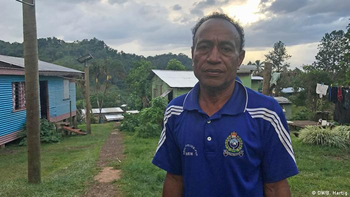A local Fijian villager standing in front of some houses