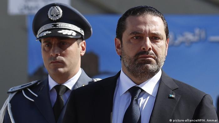 Saad Hariri standing in front of a military officer.