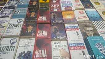 A photo of several books on a table, with the book, Asena, featured prominently.