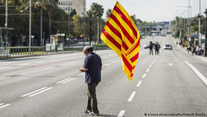 A pro-independence supporter holds a Catalan flag on the streets of Barcelona