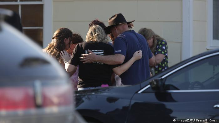 A group is gathered in prayer outside the Community Center following a shooting in Sutherland Springs, Texas (Imago/ZUMA Press/B. Owen)
