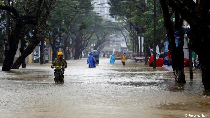 People in submerged street in Hue City, Vietnam