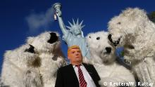 A protester wearing a mask of U.S. President Donald Trump stand along with other protesters dressed as polar bears during a demonstration under the banner Protect the climate - stop coal two days before the start of the COP 23 UN Climate Change Conference hosted by Fiji but held in Bonn, Germany November 4, 2017. REUTERS/Wolfgang Rattay TPX IMAGES OF THE DAY
