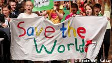 Children holding a Save the world banner (Reuters/W. Rattay)