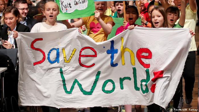 Children holding a Save the world banner