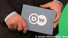 ARCHIV- Ein Moderator der Deutschen Welle hält in Bonn eine Tafel mit dem Aufdruck «DW» (Foto vom 12.04.2013). Foto: Oliver Berg/dpa (zu dpa «Kreise: Mehr Geld für die Deutsche Welle» vom 22.02.2015) +++(c) dpa - Bildfunk+++ | Verwendung weltweit