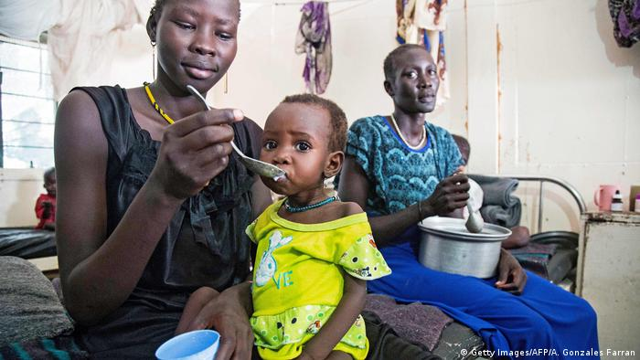A South Sudanese mother feeding her malnourished toddler