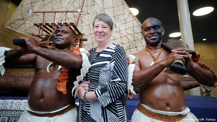 Fijan warriors in traditional clothing pose with German Environment Minister Barbara Hendricks