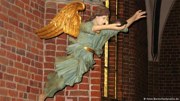 A wooden figure with wings hangs from a church ceiling.