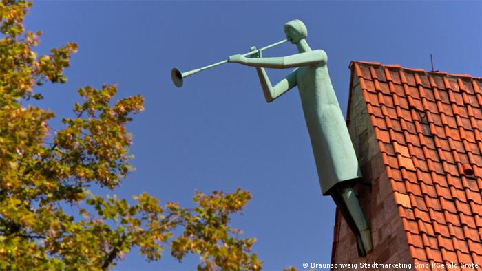 A metallic angel plays the trumpet from the roof of a church