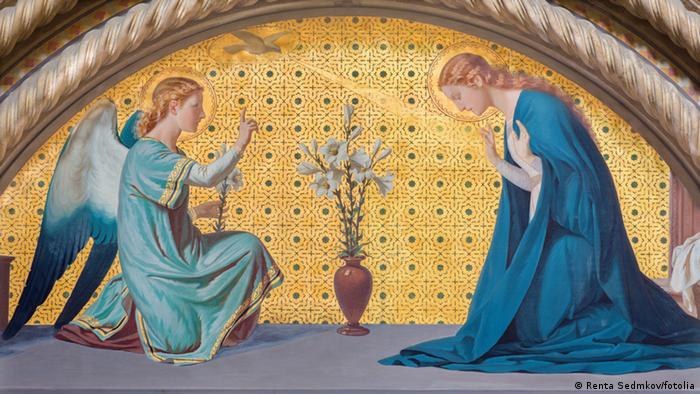 A winged angel bows in front of Mary