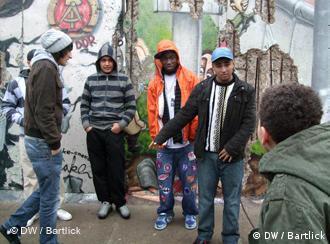 mehrere Jugendliche vor einer Mauer mit bunten Graffitis