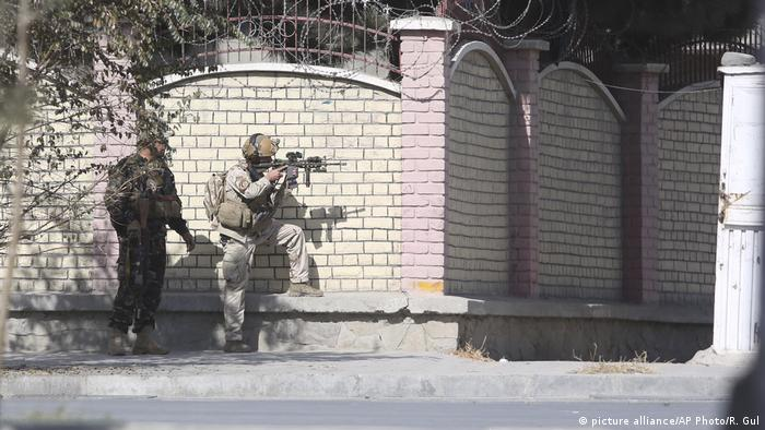 Afghan security forces take up a position near the Shamshad TV offices in Kabul