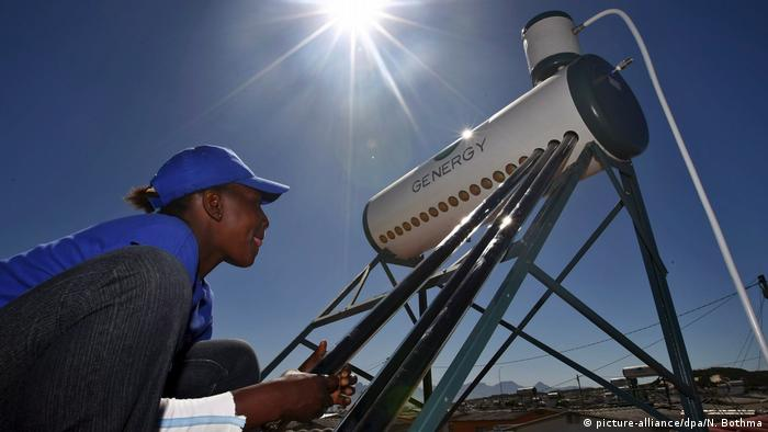 A South African woman installs a solar water heating unit on the roof of a home in Kuyasa outside Cape Town, South Africa