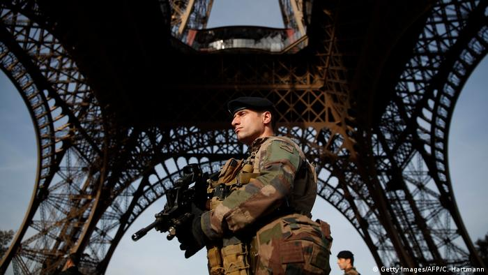 A solider stands guard with a machine gun in front of the Eifel tower