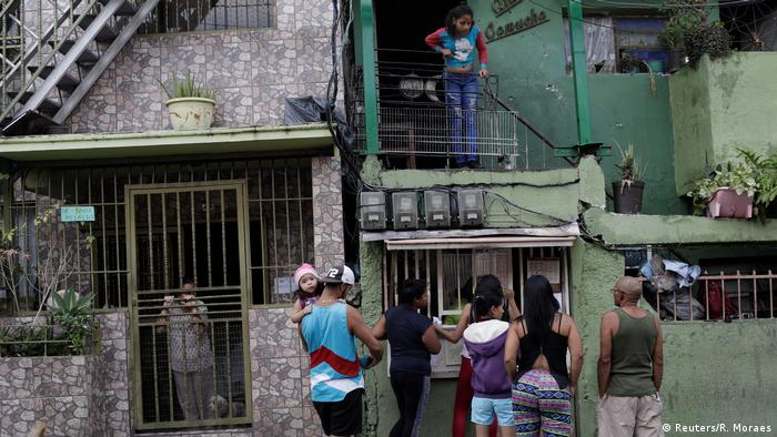 People line up in front of a gambling kiosk in Caracas (Reuters/R. Moraes)