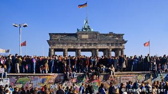 A crow of people stands atop the Berlin Wall in front of Brandenburg Gate, three German flags waving in the background