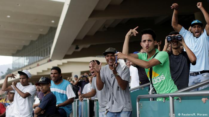 Men cheering on horses at the track (Reuters/R. Moraes)