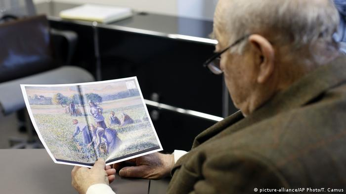 Jean Jacques Bauer, looks at a reproduction of a valuable Pissarro painting he recovered