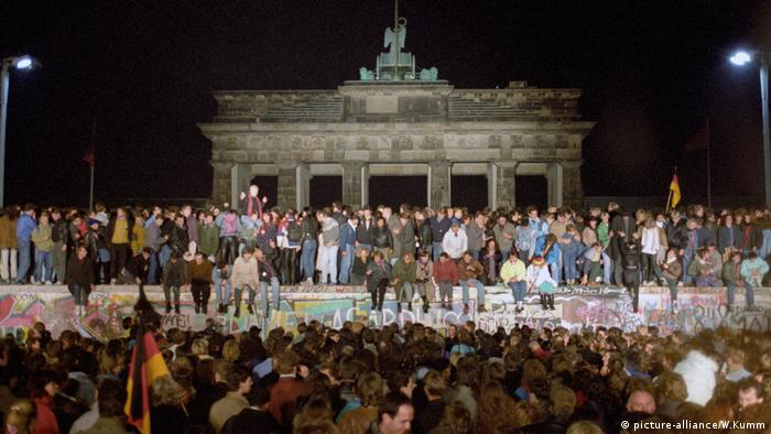 People stand on the Berlin Wall when it opened up on November 9, 1989 (picture-alliance/W.Kumm)