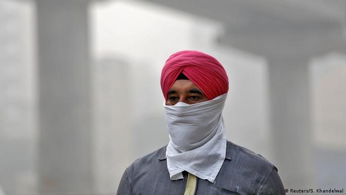 A man covers his face as he walks to work, in Delhi, India