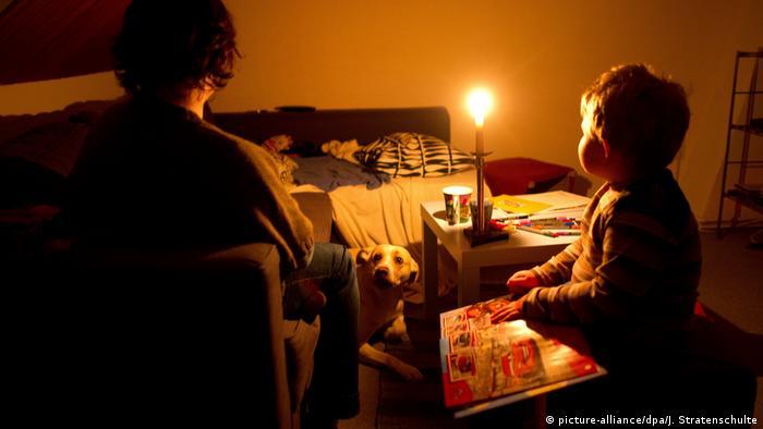 Simbol siromaštva, porodica koja ne može da plati struju, sveća gori, dečak i njegova majka