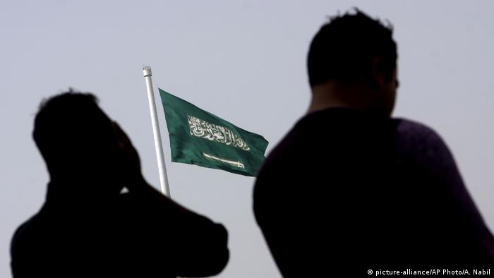 Saudi-Arabien Personen vor Flagge (picture-alliance/AP Photo/A. Nabil)