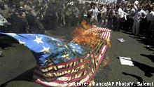 FILE- In this Friday, Aug. 13, 2004 file photo, Protesters burn a U.S. flag during a demonstration against U.S-led coalition actions in Iraq at the Enqelab (Revolution) Sq. in Tehran, Iran. (AP Photo/Vahid Salemi, File) |