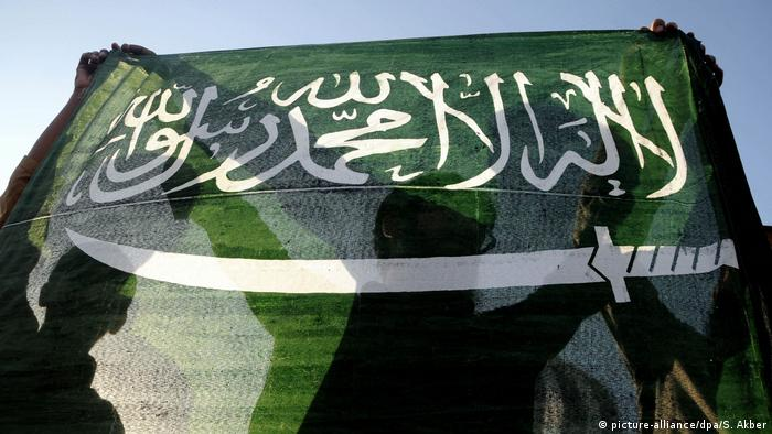 A man holds a Saudi Arabian flag