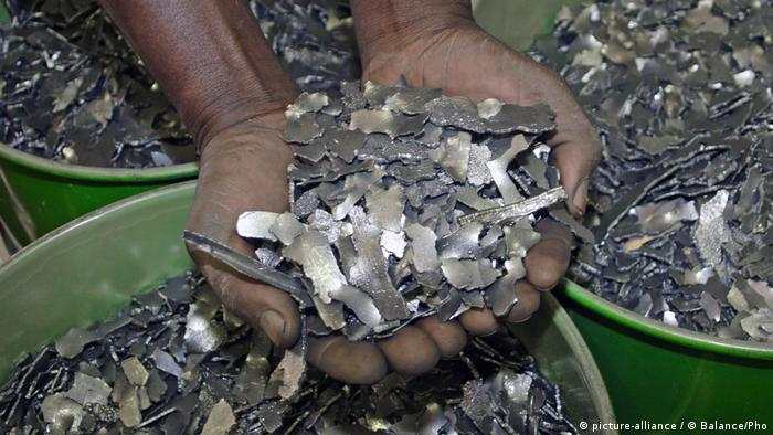 A man holds up two hands full of cobalt