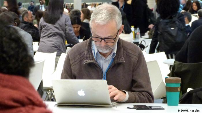 Man working on computer in crowded space