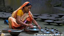 A woman gives final touch on clay pots at her courtyard. Bangladesh. Manikganj, Bangladesh.