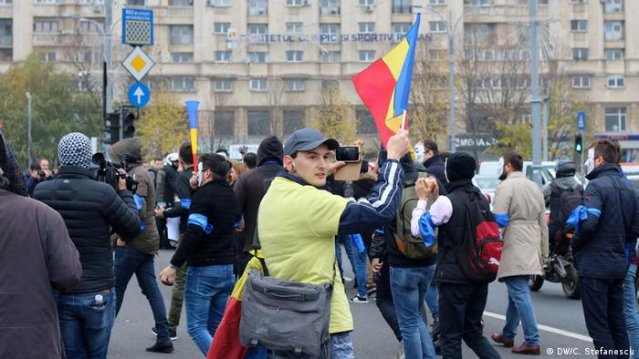 Protesters wave flags in front of the government palace in Bucharest