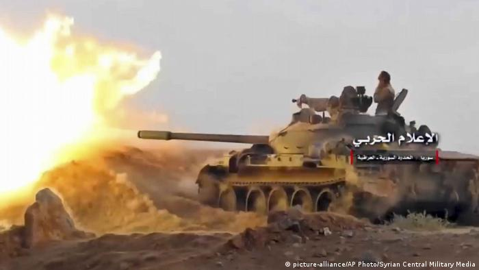 A Syrian tank fires on IS militants