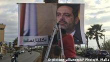 09.11.2017 Workers hang a poster of outgoing Prime Minister Saad Hariri with Arabic words that read, We are all Saad, at a seaside street in Beirut, Lebanon, Thursday, Nov. 9, 2017. Hezbollah has called on Saudi Arabia to stay out of Lebanese affairs, saying the resignation of Prime Minister Saad Hariri, announced from Riyadh over the weekend, has raised many questions. (AP Photo/Hussein Malla)  