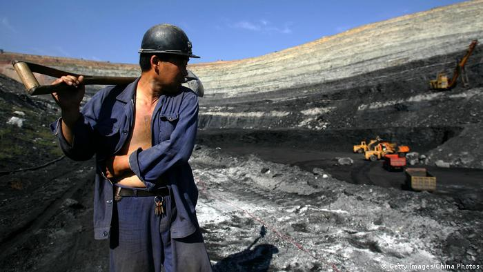 A coal miner walks on coal seams in an open pit coal mine on August 19, 2006 in Chifeng of Inner Mongolia Autonomous Region, China