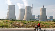 --FILE--A Chinese woman rides her electric bike past a coal-fired power plant in Huaian city, east China's Jiangsu province, 16 May 2014. China's emissions of climate-warming carbon dioxide fell in 2014 for the first time in more than a decade, offering fresh evidence that efforts to control pollution in the nation of 1.4 billion people are gaining traction. Total carbon emissions in the world's second-biggest economy dropped 2 percent in 2014 compared with the previous year, the first drop since 2001, according to a data. In the battle to rein in pollution, China has cut its dependence on coal. The nation, the world's biggest carbon emitter, has also poured money into clean energy sources such as solar, wind and hydro developments. |