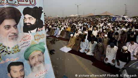 Supporters of radical religious party Tehreek-i-Labaik Ya Rasool Allah offer Friday prayers with a poster of their leaders.