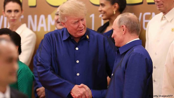 Donald Trump, US President, with his counterpart Vladimir Putin, Russia's President, dressed in Vietnamese traditional clothes.