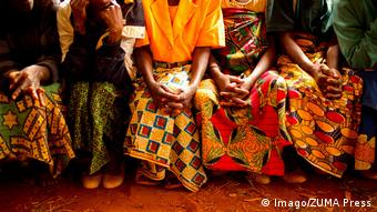From their toes to their shoulders, photos shows at least five rape victims, wearing brightly colored floor-length skirts, and blouses, sitting next to eachother on a bench.