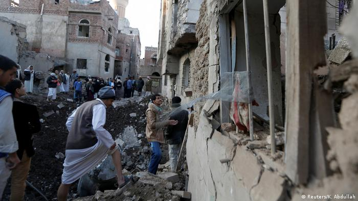 People gather at the site of an air strike in Sanaa