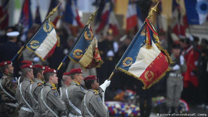 French soldiers hold aloft the national flag at the Tomb of the Unknown Soldier.