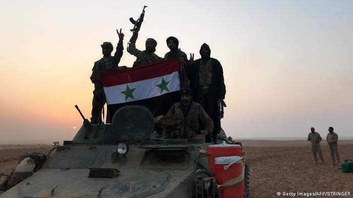 Сирийские военнослужащие радуются победе над ИГ возле Абу-Камаля