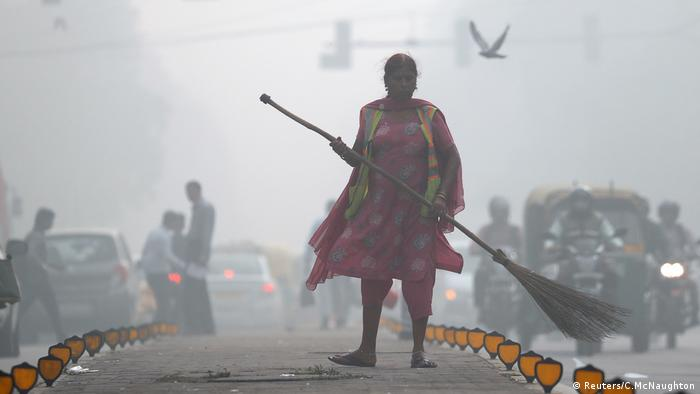 A street cleaner sweeps a road in heavy smog in Delhi